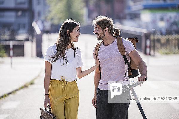 Junges Paar mit Elektroroller im Gespräch auf der Straße