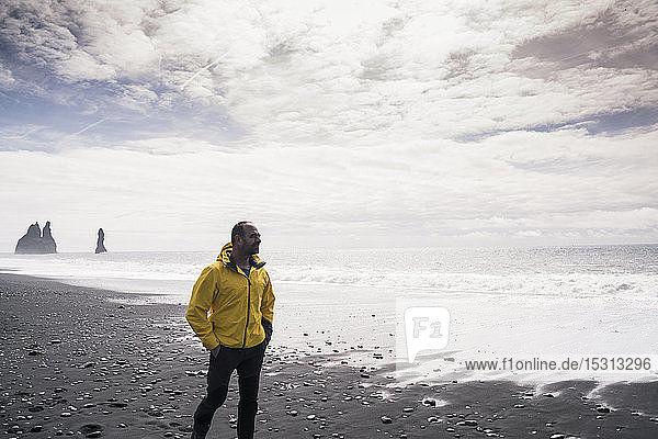 Erwachsener Mann geht an einem Lavastrand in Island