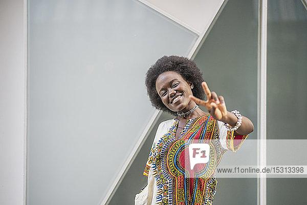 Lächelnde junge Frau steht vor geometrischem Hintergrund