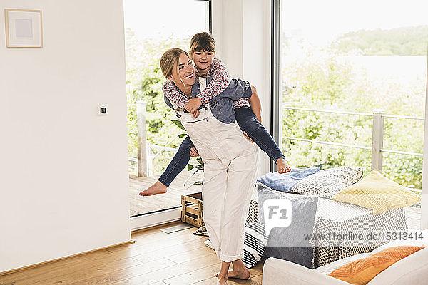Glückliche Mutter trägt Tochter huckepack zu Hause