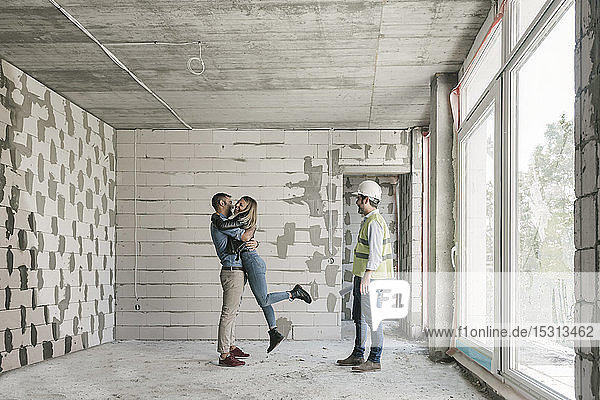 Architect having a meeting with happy future owners on construction site