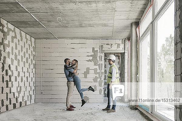 Architekt bei einem Treffen mit glücklichen zukünftigen Besitzern auf der Baustelle