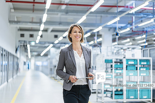 Smiling businesswoman with tablet in a modern factory