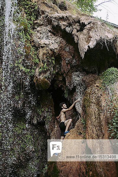 Barbusiger junger Mann klettert an einem Wasserfall