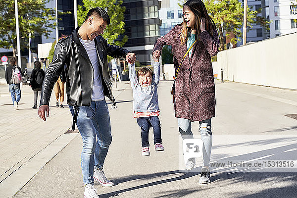 Happy parents holding hands of little girl while jumping  Barcelona  Spain