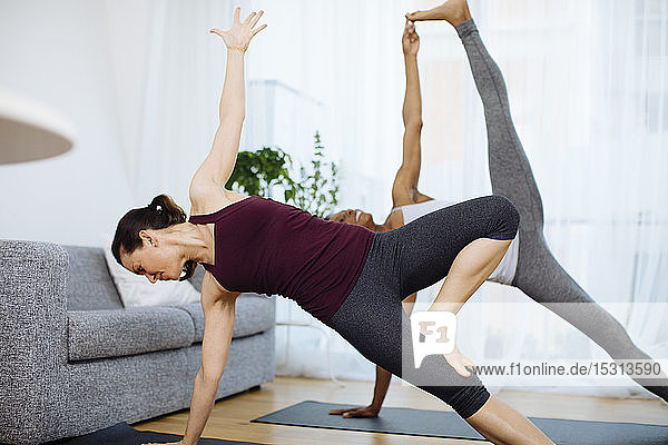 Two women practicing yoga at home