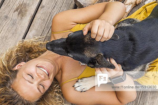 Husky-Schäferhund-Mischlingshund und sein Frauchen auf einem Holzbrett liegend