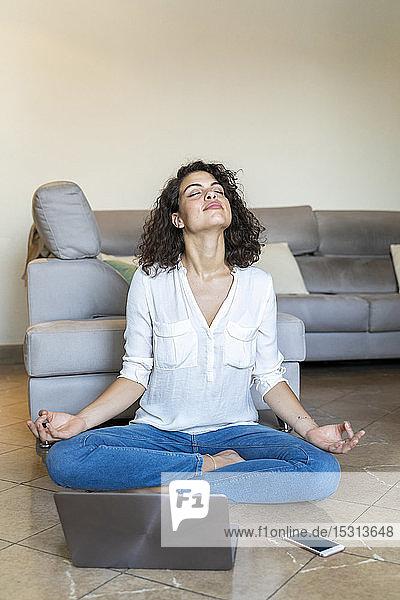 Junge Frau  die zu Hause mit Handy und Laptop auf dem Boden sitzt und Yoga macht