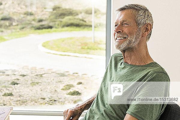 Smiling senior man sitting at the window at home