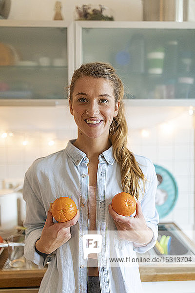 Portrait of happy young woman holding oranges at home