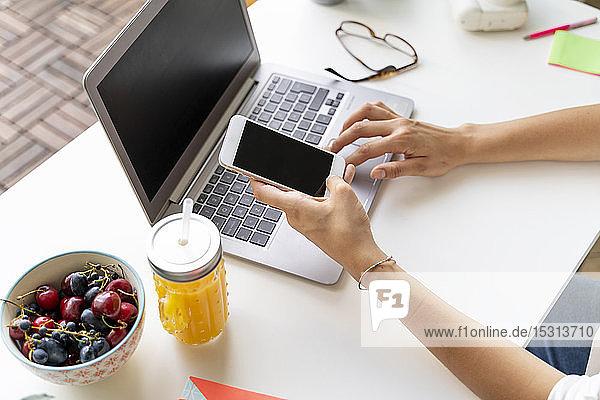 Nahaufnahme einer Frau mit Handy und Laptop am Schreibtisch mit Orangensaft und Obst