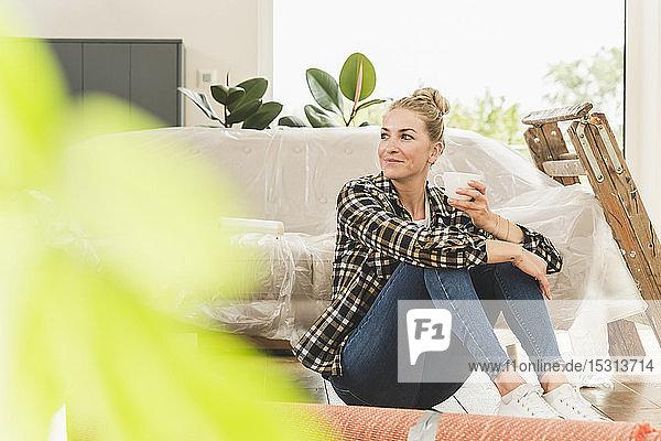 Frau sitzt in neuer Wohnung auf dem Boden und macht eine Kaffeepause