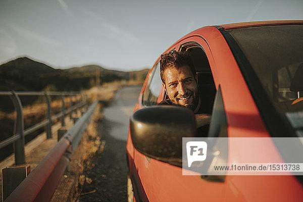 Mann auf einer Autoreise  der aus dem Autofenster schaut