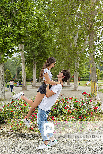 Young couple in a park  man lifting up the woman