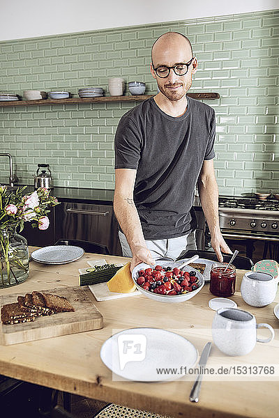 Mann deckt den Frühstückstisch