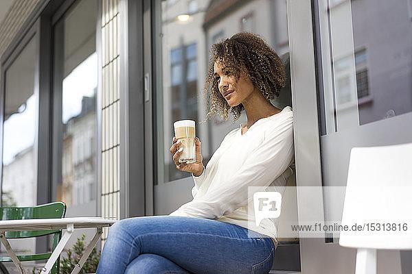 Junge Frau entspannt sich im Straßencafé mit Latte Macchiato
