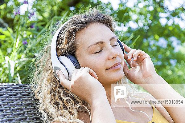 Lächelnde Frau  die mit geschlossenen Augen Musik hört und auf einem Liegestuhl liegt