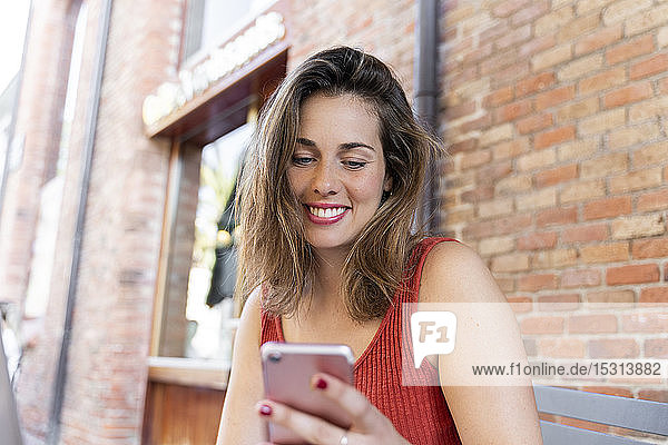 Portrait of smiling young woman looking at cell phone