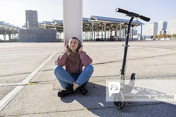 Junge Frau mit Kickroller beim Musikhören mit drahtlosen Kopfhörern  Barcelona  Spanien
