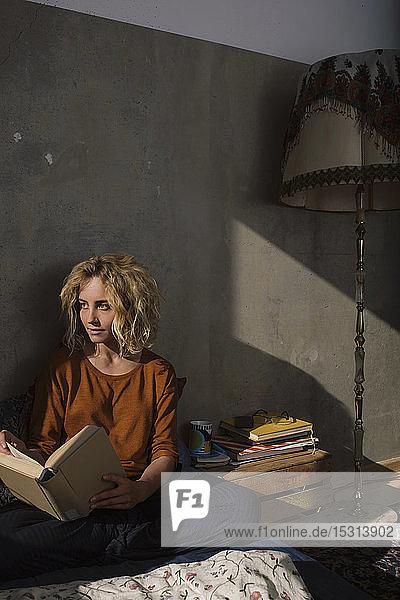Blonde Studentin sitzt mit einem Buch auf dem Bett und schaut in die Ferne