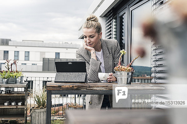 Businesswoman using tablet on roof terrace