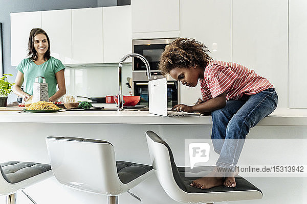 Girl sitting on kitchen counter using laptop with mother in background