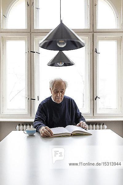 Älterer Mann liest Buch bei Tisch zu Hause