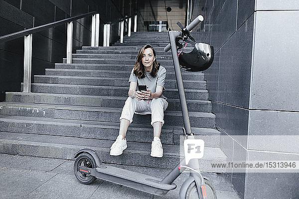 Frau mit E-Scooter und Helm  die ein Smartphone hält  auf Stufen sitzend