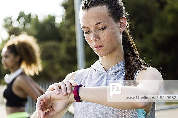 Sportliche Teenagerin bei der Kontrolle ihrer Smartwatch