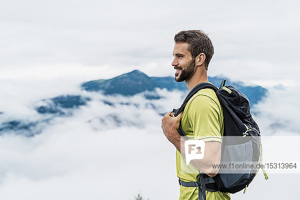 Smiling young man on a hiking trip in the mountains looking at view  Herzogstand  Bavaria  Germany