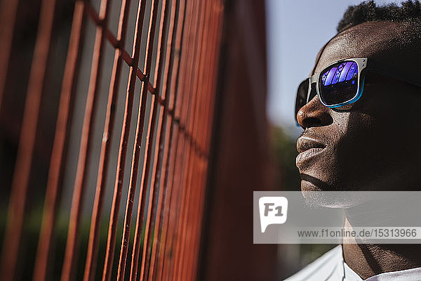 Serious young man at a fence wearing sunglasses