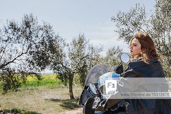 Rothaarige Frau auf Motorrad macht eine Pause  Andalusien  Spanien