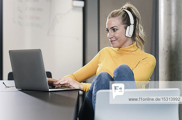 Casual businesswoman sitting at table in office using laptop and wearing headphones