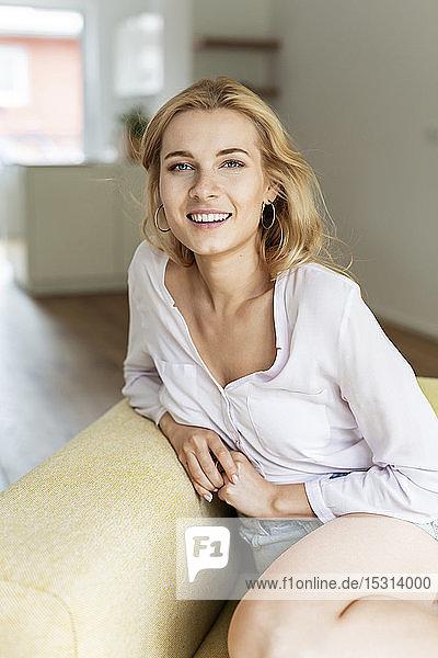 Porträt einer glücklichen jungen Frau  die auf einer Couch sitzt