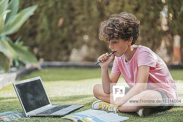 Boy doing homework in garden with laptop and workbook