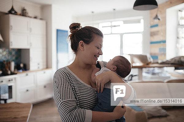 Porträt einer jungen Frau mit einem Baby zu Hause