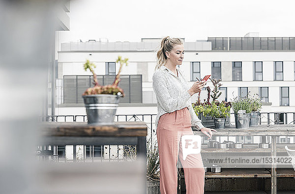 Casual businesswoman using cell phone on roof terrace