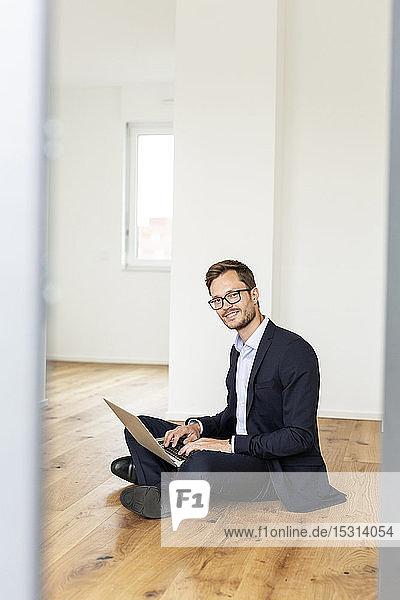 Porträt eines lächelnden Geschäftsmannes  der mit seinem Laptop auf dem Boden sitzt