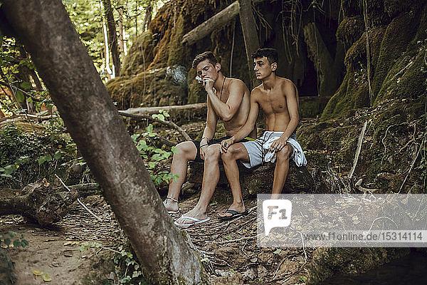 Zwei barbusige Freunde rauchen in der Natur einen Joint Marihuana