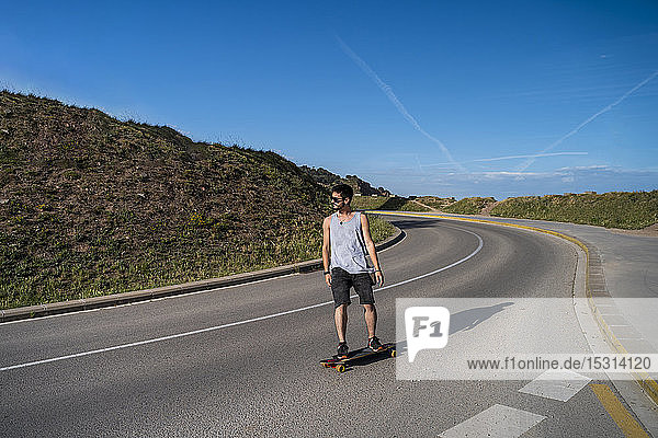 Young man longboarding on empty country road