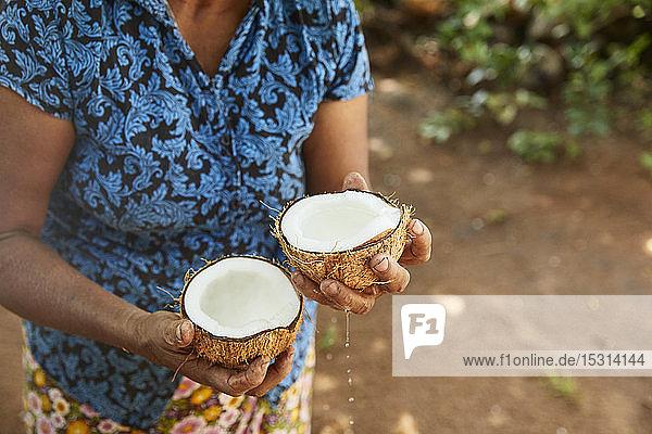 Frau hält zwei Hälften einer frischen Kokosnuss  Sri Lanka