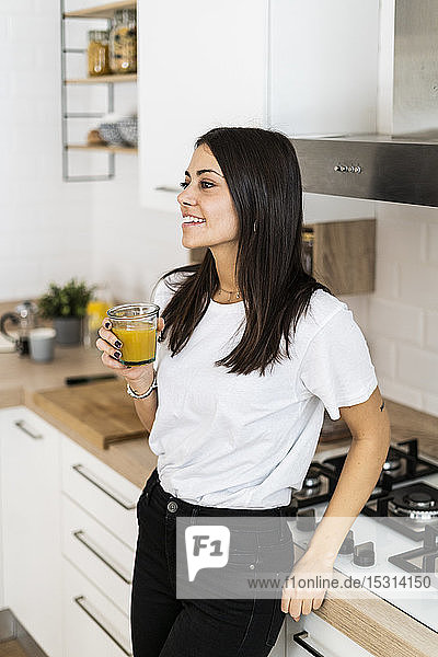 Young woman in kitchen at home drinking glass of orange juice