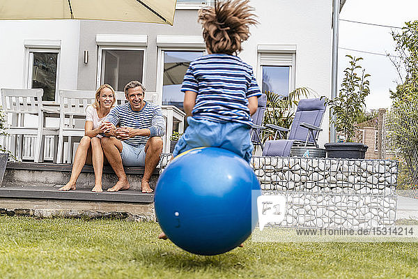 Parents watching son bouncing with hopball in garden