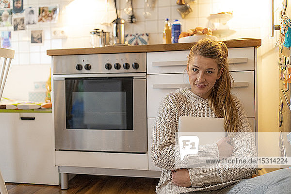 Portrait of young woman sitting on the floor in kitchen at home holding laptop
