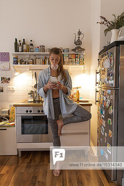 Young woman in yoga pose checking cell phone in kitchen at home
