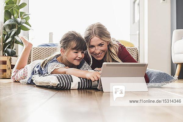Mutter und Tochter liegen zu Hause mit Tablette auf dem Boden