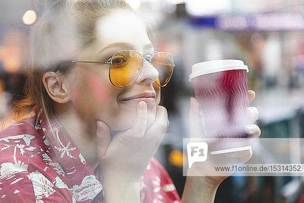 Junge Frau in einem Café  die einen Kaffee trinkt und genießt