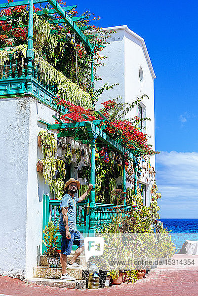 Man with hat next to house full of flowers  Lanzarote  Canary Islands  Spain