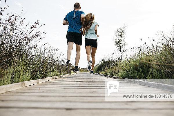 Rückansicht eines jungen Paares beim Joggen auf einem Holzlaufsteg