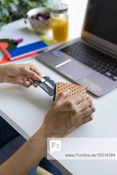 Nahaufnahme einer Frau mit Laptop  die am Schreibtisch die Karte aus der Handtasche nimmt
